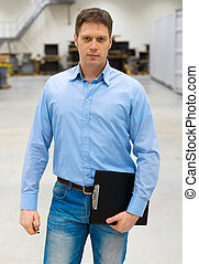 Handsome supervisor with clipboard at warehouse.