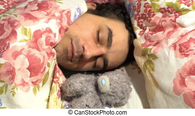 Handsome sweetheart man sleeping with plush toy, sensitive...