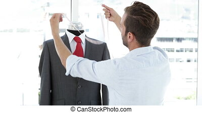 Handsome tailor measuring suit on mannequin in his studio