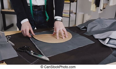 Handsome tailor working in his studio, drawing template on fabric. Creative a work of the tailor who drawing lines on the tissue with a piece of soap using sketches