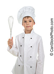 Handsome teen boy in chef uniform with a cooking whisk, on white background.