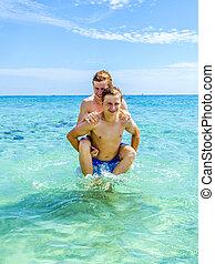teen have fun playing piggyback in the ocean