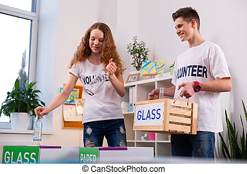 Handsome teenager smiling while sorting glass with his friend