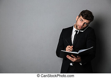 Handsome thinking businessman taking notes while talking on mobile phone, lookin aside
