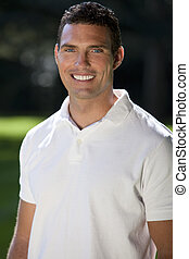 Portrait of a handsome man in his thirties wearing a white polo shirt outside in a sunlit green field.