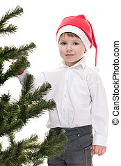 Handsome toddler in christmas hat decorating new year tree