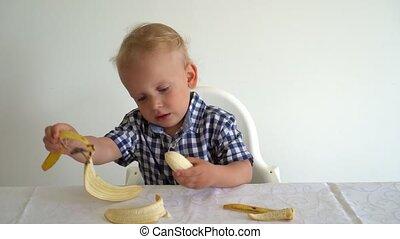 Handsome toddler is eating yellow banana. Gimbal motion shot...