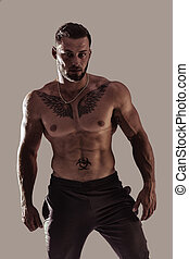 Handsome topless muscular man standing