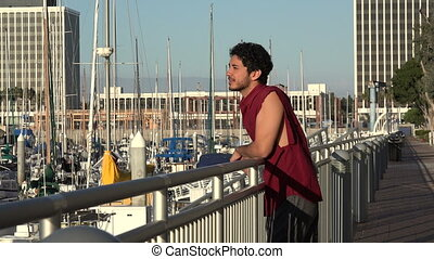 Handsome tourist looking at sail boats