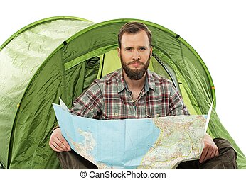 Handsome traveler in a tent with a map planning route