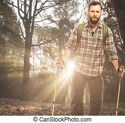 Handsome traveler with backpack and hiking poles in autumnal forest
