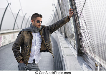Handsome trendy young man standing on a sidewalk wearing a fashionable jacket and scarf in a relaxed confident pose looking away down the bridge