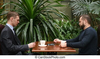 Handsome two businessmen have a meeting in cafe