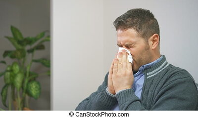 Handsome unshaved man blowing nose to napkin.