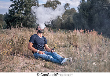 Handsome vape man enjoying an electronic smoke device on the grass. Non-tobacco smoking.