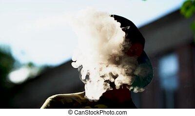 Handsome vaper blows smoke through his nose. - Charming...