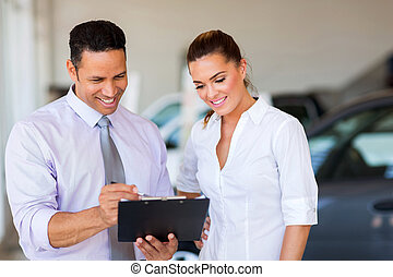 vehicle dealership principal and saleswoman looking at clipboard