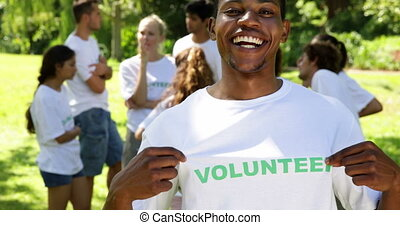Handsome volunteer showing his tshirt to camera on a sunny day
