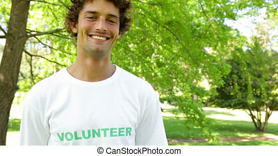 Handsome volunteer smiling at the camera on a sunny day