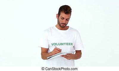 Handsome volunteer writing on note