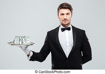 Handsome waiter in tuxedo standing and holding money on tray...