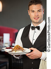 Handsome waiter serving appetizing duck dish in classy...