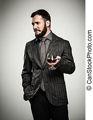Handsome well-dressed man in jacket with glass of beverage