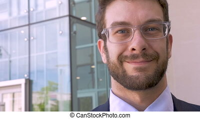 Handsome well dressed man portrait smiling outside glass office building