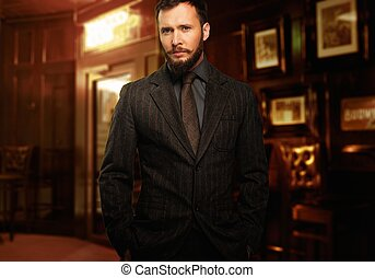 Handsome well-dressed man with beard in jacket and tie