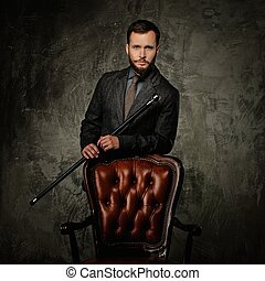 Handsome well-dressed man with stick standing near leather chair