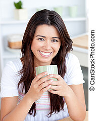 Handsome woman drinking coffee in the kitchen