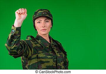 Handsome women in military uniforms show fist to the camera. Empty side space and green background.