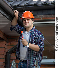 Handsome worker in hardhat posing with hammer on step ladder