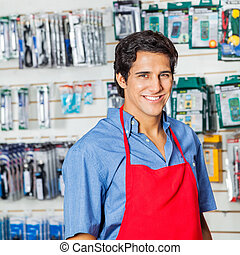 Handsome Worker In Red Apron Smiling At Hardware Shop