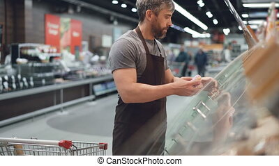 Handsome worker of hypermarket is taking doughnuts from...