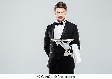 Handsome yong waiter in tuxedo and gloves holding empty tray...