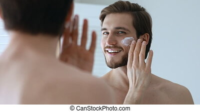Handsome young adult man applying facial cream moisturizer looking in bathroom mirror. Smiling sexy shirtless bearded guy doing morning skin care beauty routine. Male skincare treatment concept.