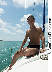 Handsome young adult man sailing on yacht