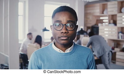 Handsome young African American businessman in glasses...