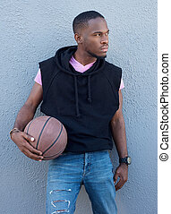 Handsome young african american man holding basketball