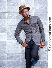 Handsome young african american man leaning against wall