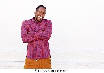 Handsome young african man laughing with arms crossed