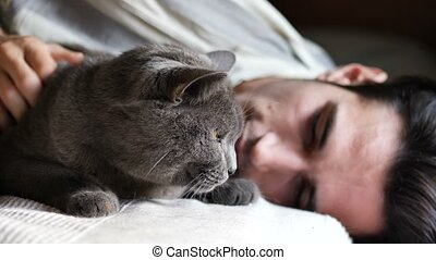 Handsome Young Animal-Lover Man on a Bed, Hugging and Cuddling his Gray Domestic Cat Pet.