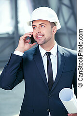 Handsome young architect is using telephone for communication