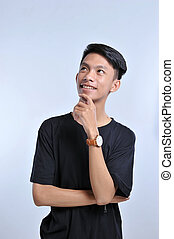 Handsome young asian boy wearing black t-shirt and wristwatch with hand on chin thinking about question, pensive expression. Smiling with thoughtful face. Doubt concept