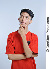 Handsome young asian boy wearing orange t-shirt with hand on chin thinking about question, pensive expression. Smiling with thoughtful face. Doubt concept