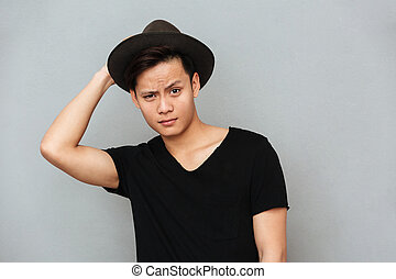 Handsome young asian man standing isolated over grey wall
