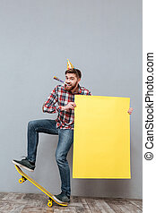 Handsome young bearded birthday man on skateboard holding copyspace board