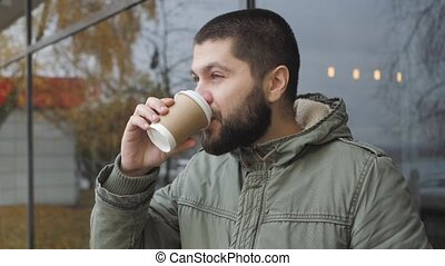 Handsome young bearded man is holding a cup. drinking hot drink coffee or tea in autumn outdoors