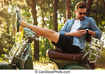 Handsome young bearded man sitting on scooter outdoors